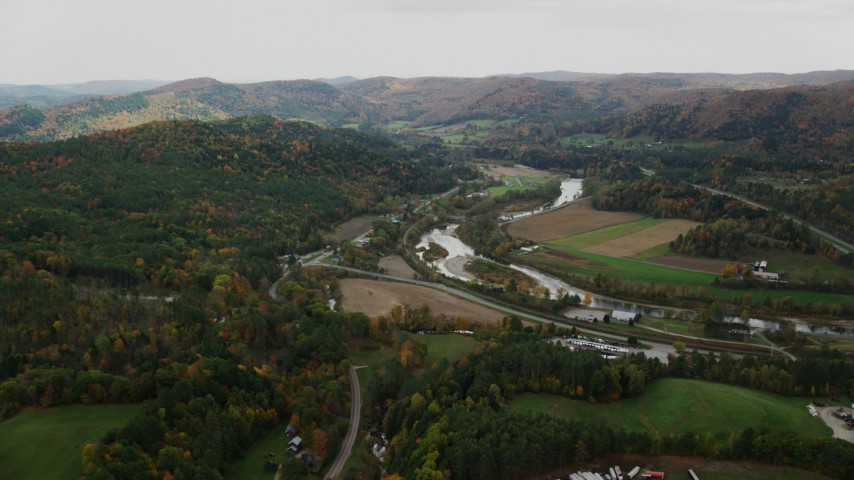 Fly over trailers, approaching White River, Route 107 in autumn, South Royalton, Vermont Aerial Stock Footage | AX150_423