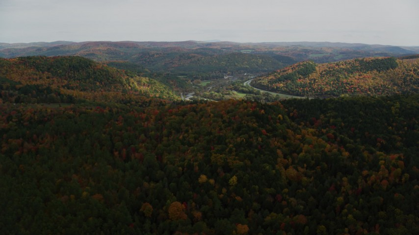 Fly over colorful forest, hills, approach small farms, autumn, South Royalton, Vermont Aerial Stock Footage | AX150_425