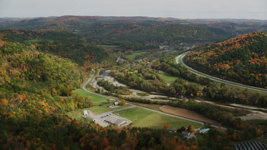 6K stock footage aerial video flying over forest, small farms, approach Route 14, White River, autumn, South Royalton, Vermont Aerial Stock Footage | AX150_426