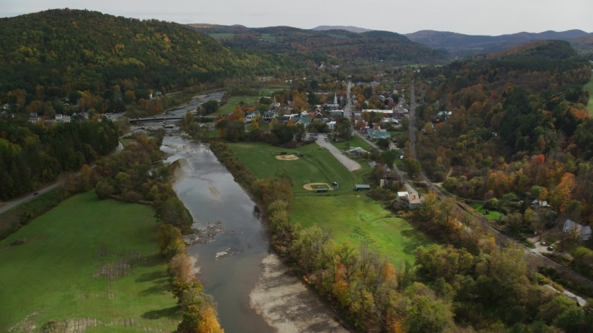 Fly by small bridge, White River, small rural town, autumn, South Royalton, Vermont Aerial Stock Footage | AX150_428