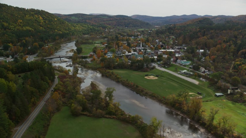 6K stock footage aerial video flying by small bridge, White River, small rural town, autumn, South Royalton, Vermont Aerial Stock Footage | AX150_428