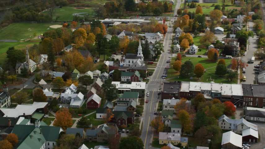 Orbiting homes, churches and town square in small rural town, autumn, South Royalton, Vermont Aerial Stock Footage | AX150_434