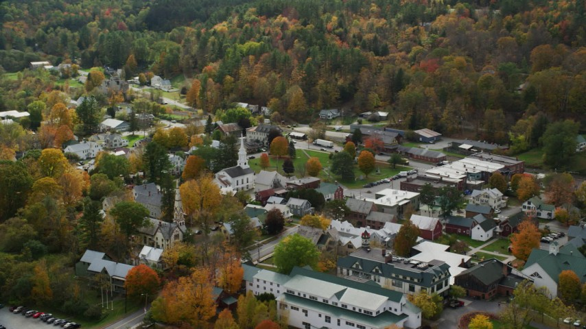 Orbiting small rural town, colorful foliage in autumn, South Royalton, Vermont Aerial Stock Footage | AX150_435