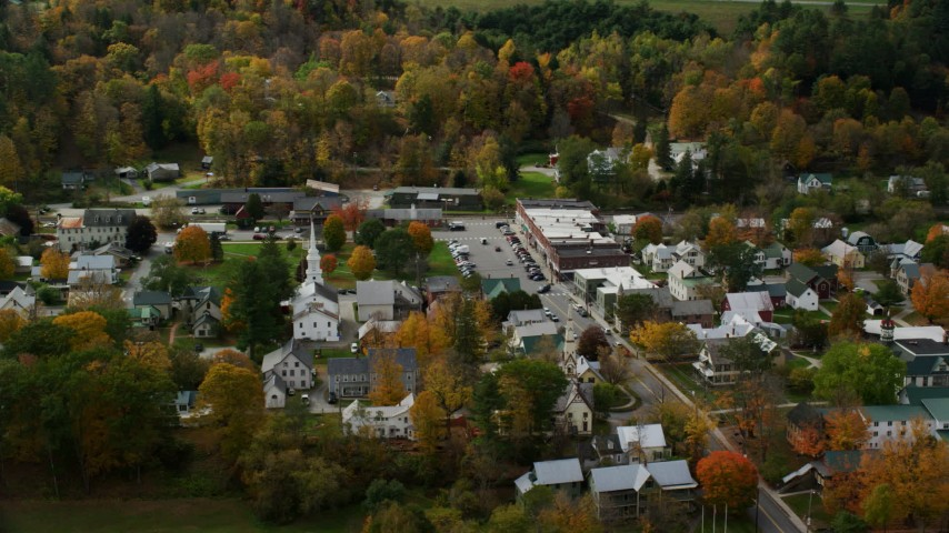 Orbiting a small rural town and town square with colorful autumn trees, South Royalton, Vermont Aerial Stock Footage | AX150_436