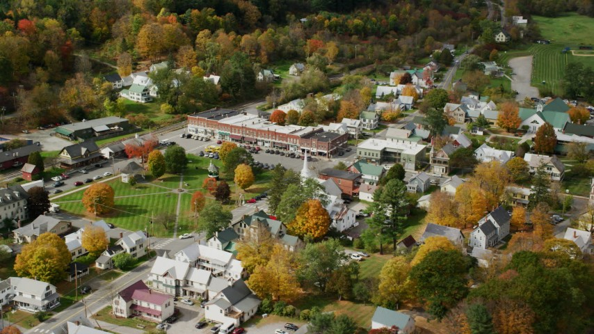 Orbiting town square, row of shops, colorful foliage in small town, autumn, South Royalton, Vermont Aerial Stock Footage | AX150_437
