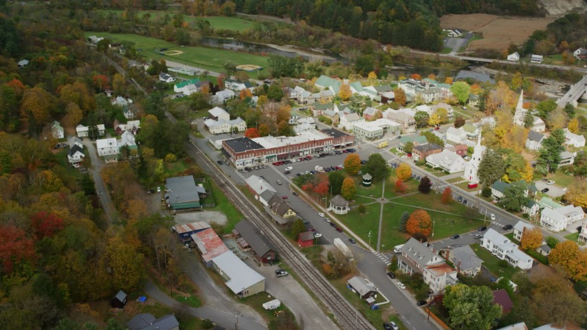 Orbit small rural town, town square, churches, shops, autumn, South Royalton, Vermont Aerial Stock Footage AX150_438