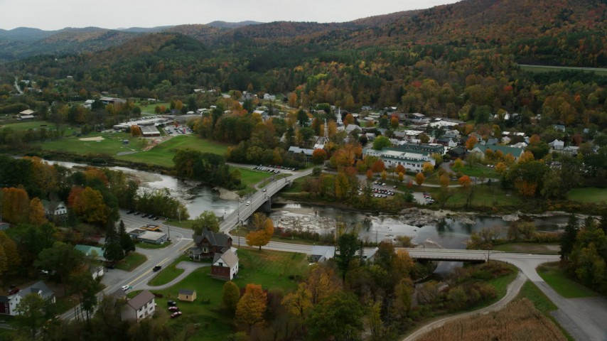 Fly over small bridge, White River, approach churches, small town, autumn, South Royalton, Vermont Aerial Stock Footage | AX150_441