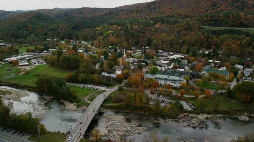6K stock footage aerial video flying over small bridge, White River, approach churches, small town, autumn, South Royalton, Vermont Aerial Stock Footage | AX150_441