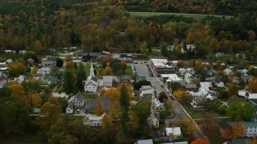 Orbiting colorful foliage throughout small rural town adjacent to the town square, autumn, South Royalton, Vermont Aerial Stock Footage | AX150_442