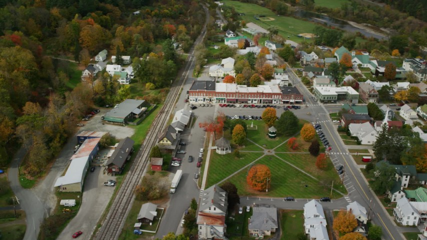 Orbiting small rural town in autumn, town square, shops, churches, South Royalton, Vermont Aerial Stock Footage | AX150_443