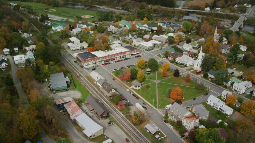 6K stock footage aerial video orbiting small rural town in autumn, town square, shops, churches, South Royalton, Vermont Aerial Stock Footage | AX150_443