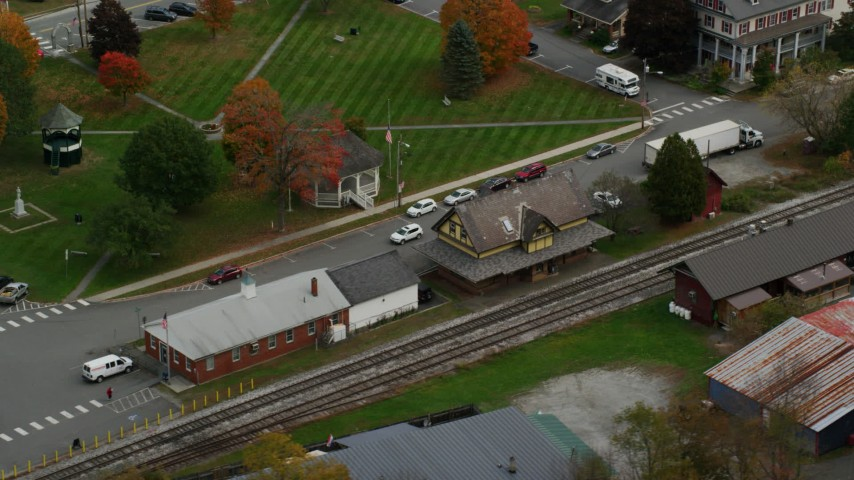 Orbiting railroad tracks and station, small rural town, autumn, South Royalton, Vermont Aerial Stock Footage | AX150_444