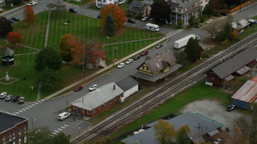 6K stock footage aerial video orbiting railroad tracks and station, small rural town, autumn, South Royalton, Vermont Aerial Stock Footage | AX150_444
