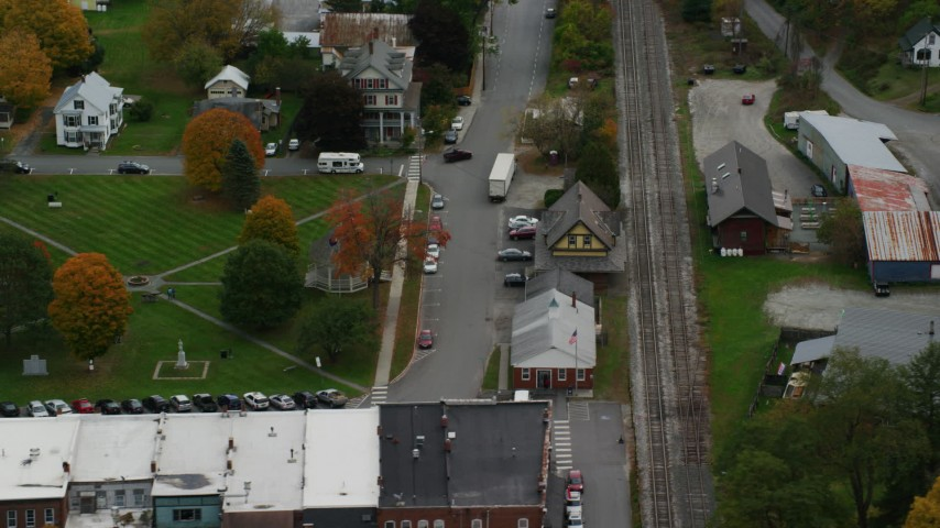 Orbit railroad tracks and station, town square, small town, autumn, South Royalton, Vermont Aerial Stock Footage | AX150_445