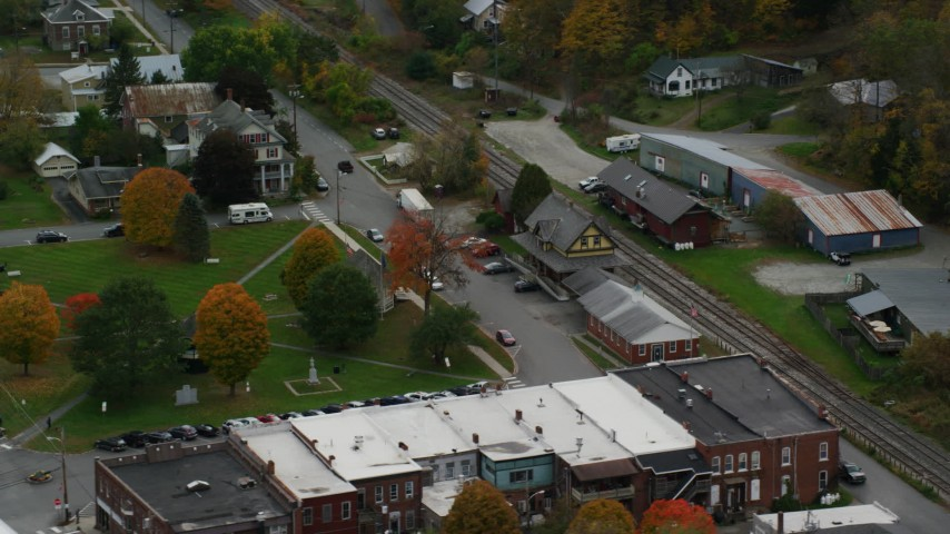 6K stock footage aerial video orbiting railroad tracks and station, town square, small town, autumn, South Royalton, Vermont Aerial Stock Footage | AX150_445