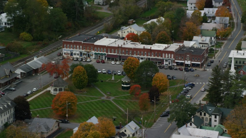 Fly away from shops and town square in small rural town, autumn, South Royalton, Vermont Aerial Stock Footage | AX150_448
