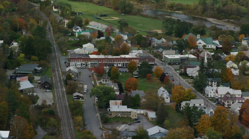 Flying away from small rural town, shops, town square, autumn, South Royalton, Vermont Aerial Stock Footage | AX150_449