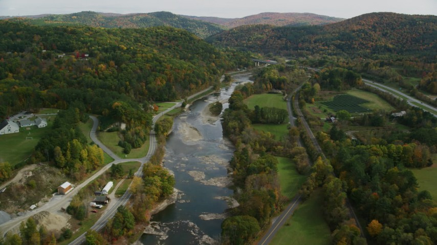 Flying over White River, roads, approaching small bridge, autumn, South Royalton, Vermont Aerial Stock Footage | AX150_451