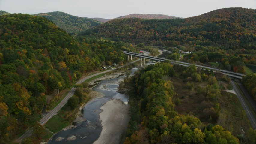 Fly over White River, approach Interstate 89, small bridge, pan left, autumn, South Royalton, Vermont Aerial Stock Footage | AX150_452