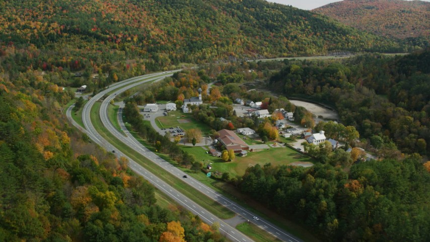 6K stock footage aerial video flying by Interstate 89 through small rural town, autumn, Sharon, Vermont Aerial Stock Footage | AX150_454