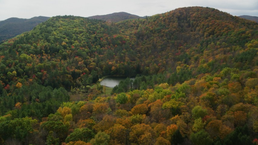 6K stock footage aerial video tilting down over pond, brightly colored forested hills in autumn, Sharon, Vermont Aerial Stock Footage | AX150_458