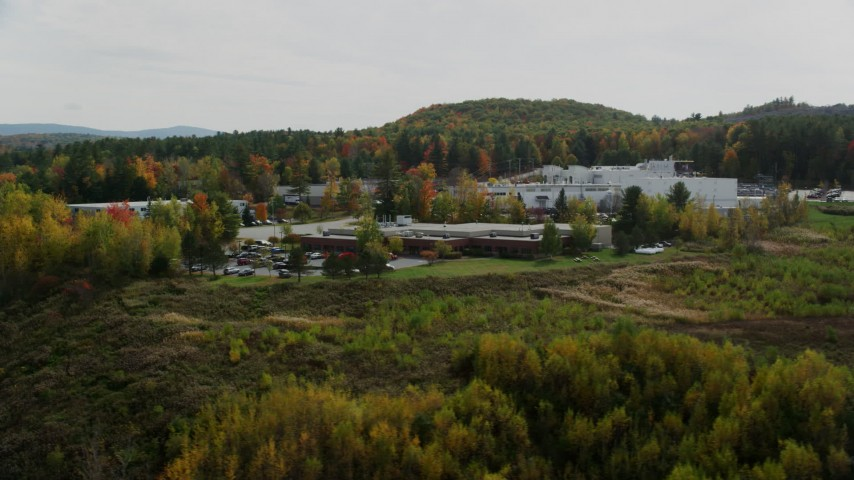 6K stock footage aerial video flying by office buildings, colorful foliage, cloudy skies, autumn, Lebanon, New Hampshire Aerial Stock Footage | AX150_476