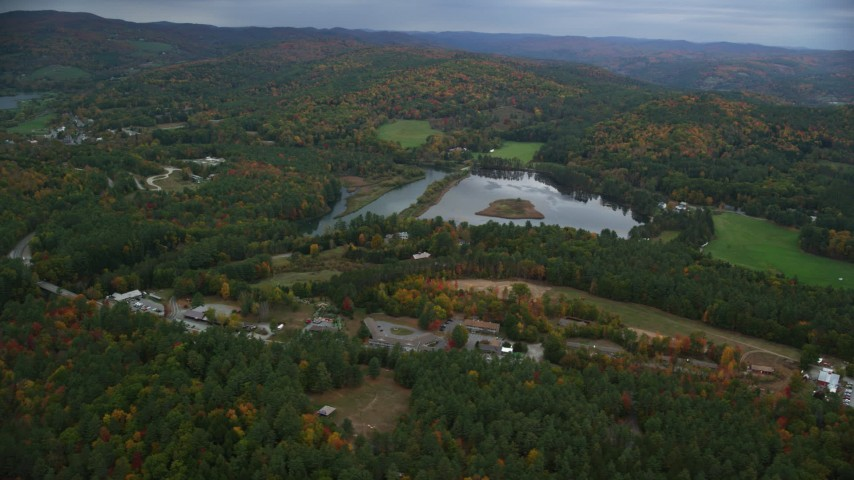 6K stock footage aerial video flying by Dewey's Pond, rural homes, autumn, overcast, Quechee, Vermont Aerial Stock Footage | AX151_005