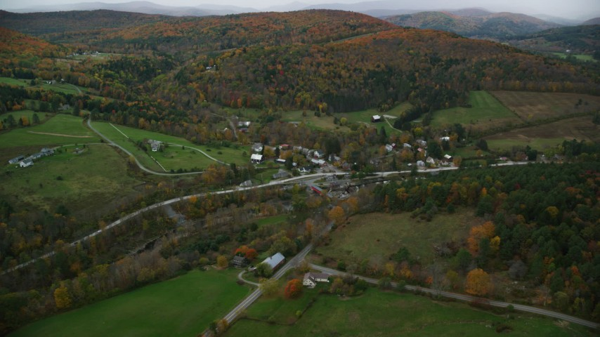 6K stock footage aerial video approaching small rural town, tilt down over bridge spanning Ottauquechee River, autumn, Taftsville, Vermont Aerial Stock Footage | AX151_009