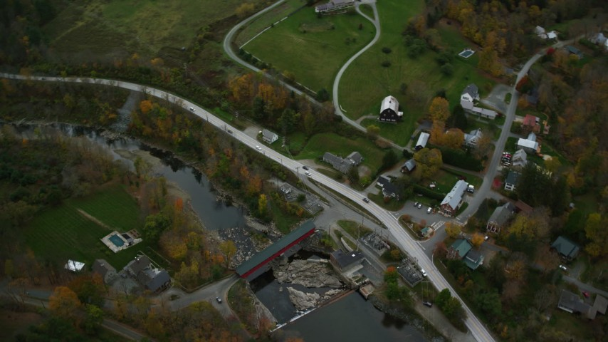 6K stock footage aerial video of a bird's eye view flying away from bridge, Ottauquechee River, small town, autumn, Taftsville, Vermont Aerial Stock Footage | AX151_010