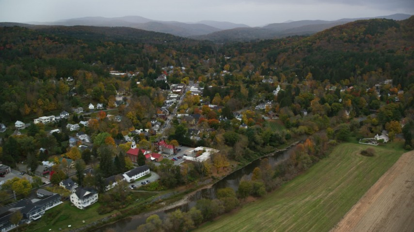 6K stock footage aerial video flying by the Ottauquechee River, small rural town, autumn, Woodstock, Vermont Aerial Stock Footage | AX151_013