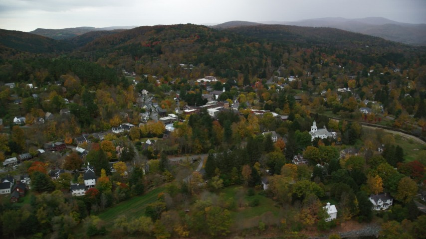 6K stock footage aerial video flying by Ottauquechee River, small rural town, overcast, autumn, Woodstock, Vermont Aerial Stock Footage | AX151_014