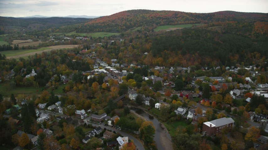 6K stock footage aerial video orbiting small rural town, Ottauquechee River, overcast, autumn, Woodstock, Vermont Aerial Stock Footage | AX151_016