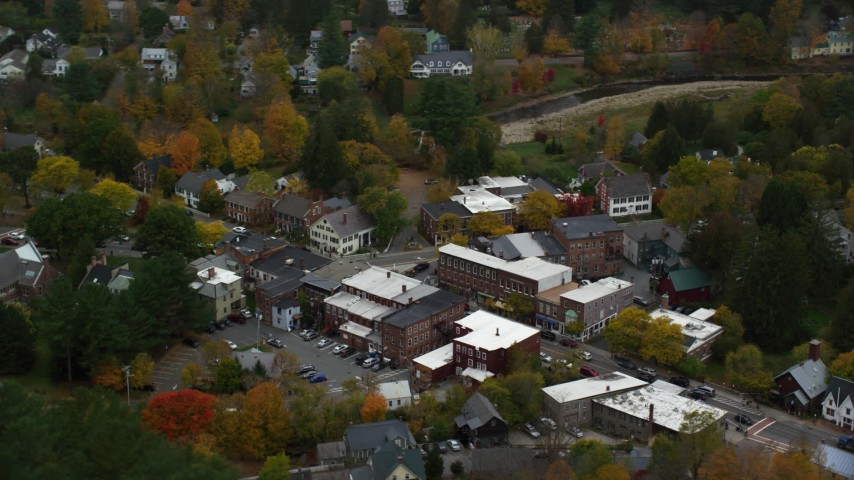 6K stock footage aerial video orbiting small rural town, brightly colored trees in autumn, Woodstock, Vermont Aerial Stock Footage | AX151_018