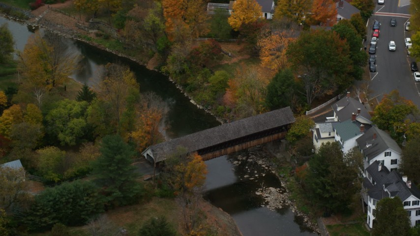 6K stock footage aerial video orbiting a covered bridge, Ottauquechee River, autumn, Woodstock, Vermont Aerial Stock Footage | AX151_021