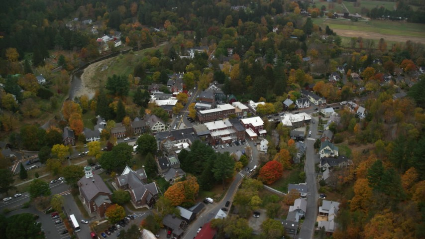 6K stock footage aerial video flying by small rural town with s small bridge, river, autumn, Woodstock, Vermont Aerial Stock Footage | AX151_022