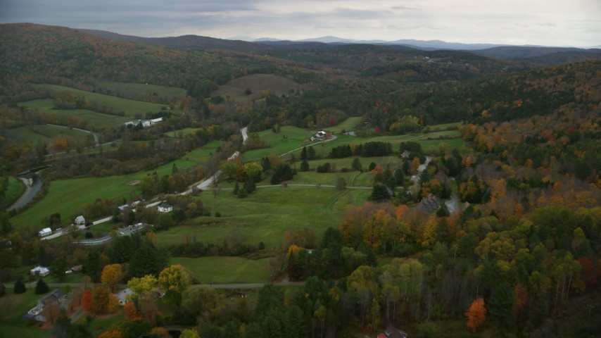 6K stock footage aerial video flying over rural homes, grassy clearings, colorful foliage, autumn, Woodstock, Vermont Aerial Stock Footage | AX151_023