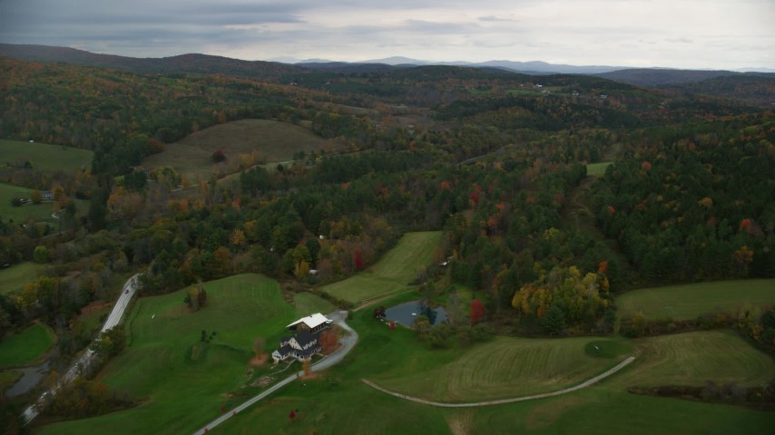 6K stock footage aerial video flying over rural homes, approaching colorful forests, hills, autumn, Woodstock, Vermont Aerial Stock Footage | AX151_024