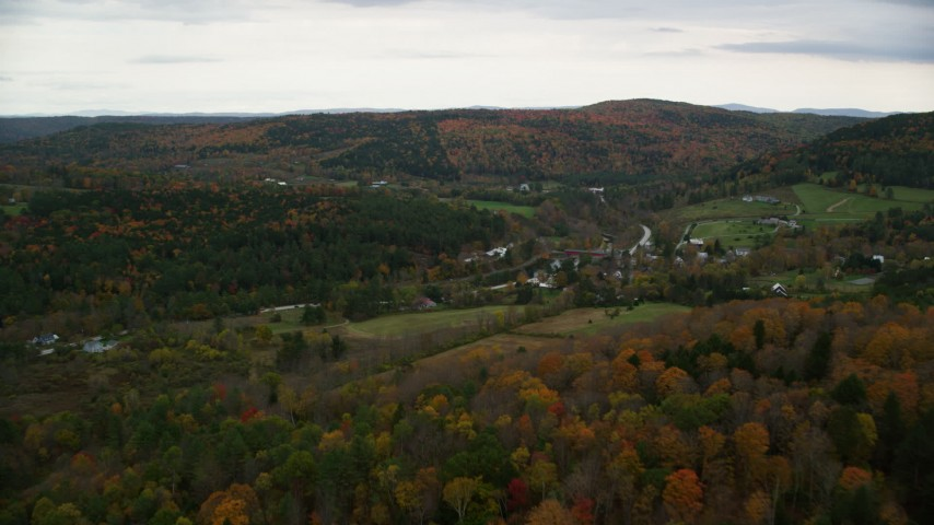 6K stock footage aerial video flying over colorful forest, approach farms, small rural town, autumn, Taftsville, Vermont Aerial Stock Footage | AX151_025