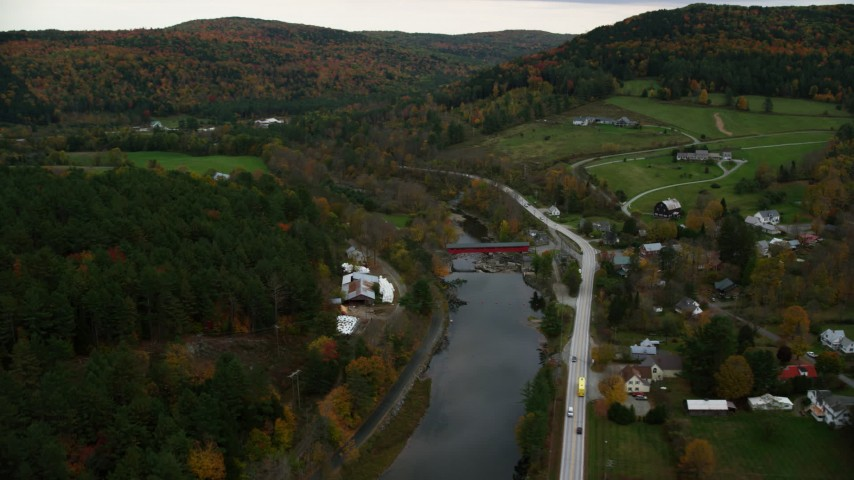 6K stock footage aerial video flying by small rural town, Ottauquechee River, small covered bridge, autumn, Taftsville, Vermont Aerial Stock Footage | AX151_026
