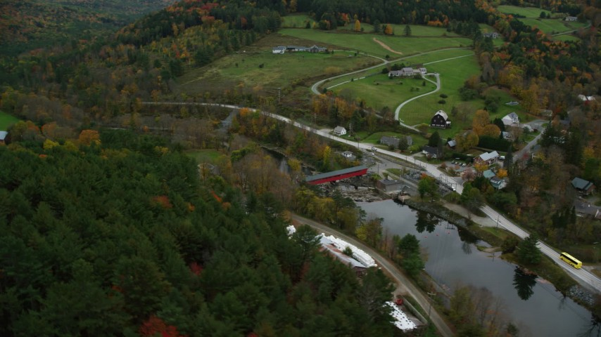 6K stock footage aerial video flying by small covered bridge, Ottauquechee River, small rural town, autumn, Taftsville, Vermont Aerial Stock Footage | AX151_027