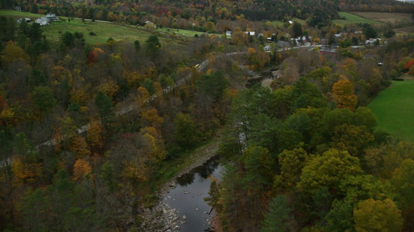 6K stock footage aerial video flying over Ottququechee River, approach small rural town, autumn, Taftsville, Vermont Aerial Stock Footage | AX151_028