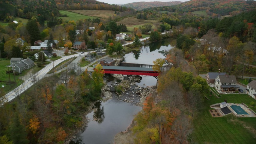 6K stock footage aerial video approaching small covered bridge across Ottauquechee River, autumn, Taftsville, Vermont Aerial Stock Footage | AX151_029