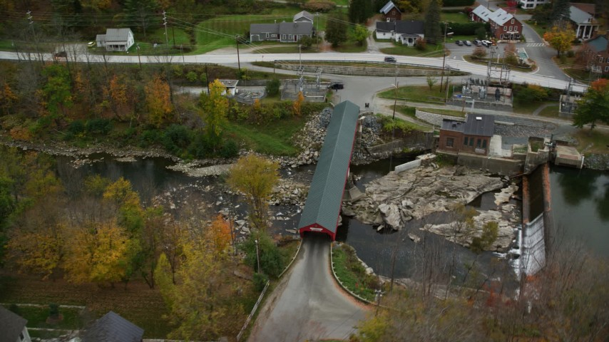 6K stock footage aerial video approaching small rural town, reveal covered bridge, Ottauqueche River, autumn, Taftsville, Vermont Aerial Stock Footage | AX151_035