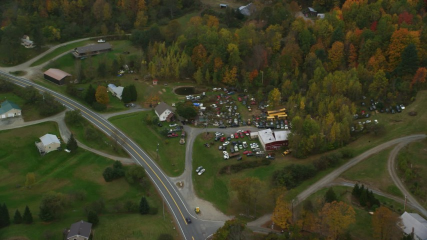 6K stock footage aerial video flying by rural homes, colorful trees, tilt down over car junkyard, autumn, Hartland, Vermont Aerial Stock Footage | AX151_040
