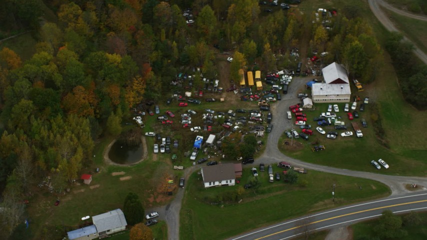 6K stock footage aerial video flying by rural homes, car junkyard, autumn, Hartland, Vermont Aerial Stock Footage | AX151_041