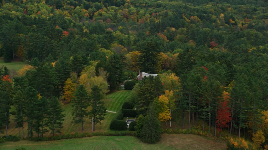 6K stock footage aerial video flying by colorful trees, revealing isolated mansion, autumn, Cornish, New Hampshire Aerial Stock Footage | AX151_051