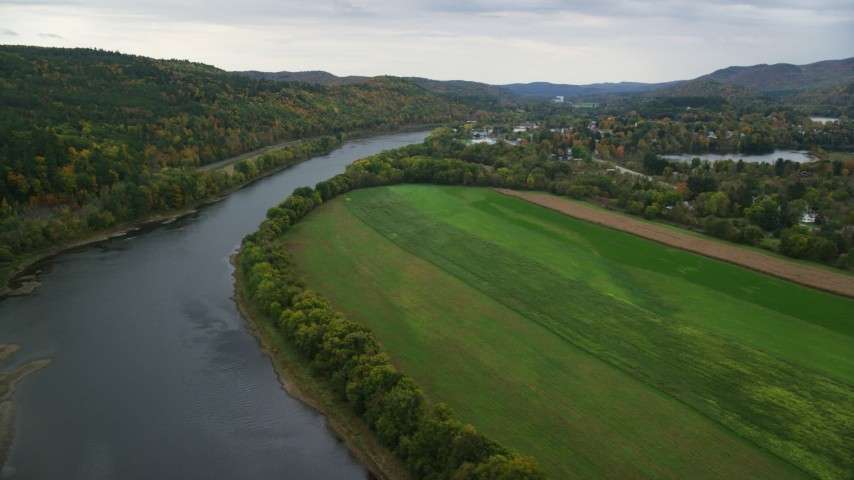 6K stock footage aerial video flying over Connecticut River, approaching small town, autumn, Windsor, Vermont Aerial Stock Footage | AX151_055