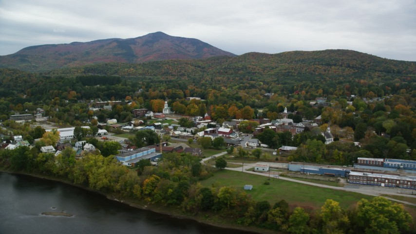 6K stock footage aerial video flying by small rural town, colorful foliage in autumn, overcast, Windsor, Vermont Aerial Stock Footage | AX151_057