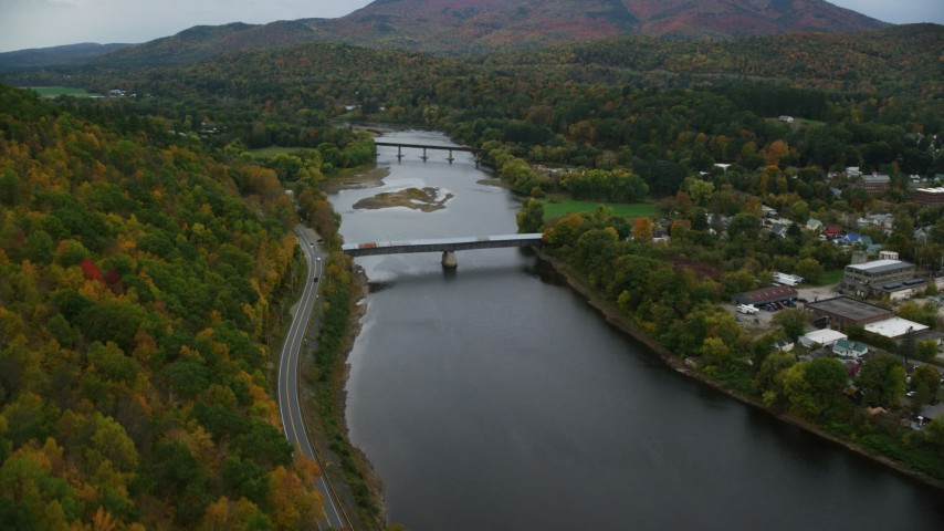 6K stock footage aerial video flying by covered bridge, Connecticut River, colorful trees, autumn, Windsor, Vermont Aerial Stock Footage | AX151_058