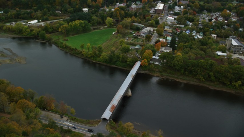 6K stock footage aerial video orbiting covered bridge spanning the Connecticut River, autumn, Windsor, Vermont Aerial Stock Footage | AX151_059